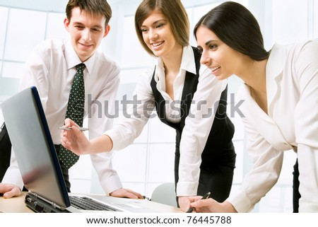 Successful businesspeople looking at monitor of computer