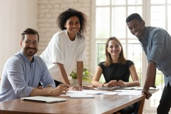 Successful businesspeople portrait, promoted employees, creative department workgroup working on common project concept. Five multi-ethnic business people gather in boardroom smiling posing for camera
