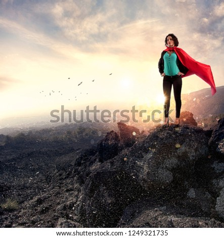 Successful businesswoman acts like a super hero on a mountain. Concept of determination and success #1249321735