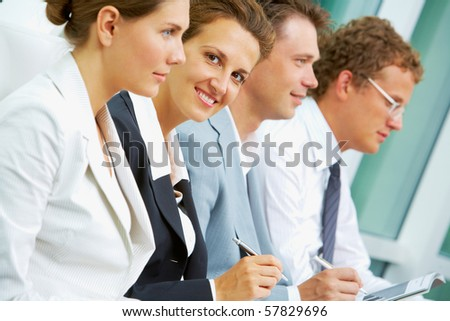 Successful businesswoman looking at camera while working between partners