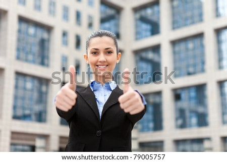 successful businesswoman outdoor showing thumbs up