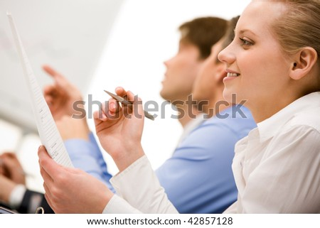 Successful businesswoman reading paper in working environment