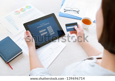 Successful businesswoman sitting at desk in casual clothes and inputting her password and login to carry out online banking operation on digital tablet in the office