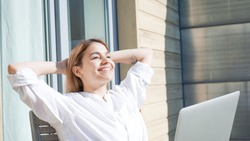 Successful businesswoman smiling and enjoying life. Independent woman manager working from home and sunbathing on a sunny day at home.