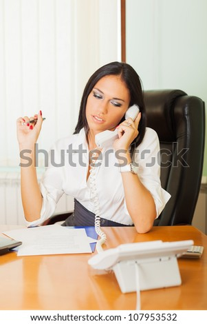 Successful businesswoman with phone at office