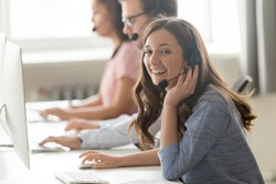 Successful call center professional telemarketing representative portrait concept. Service phone operator woman works with associates sitting on shared desk wears headset use computer looks at camera