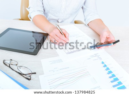Successful caucasian businesswoman sitting at desk in casual clothes and using modern devices for analyzing sales statistics for the month period of time