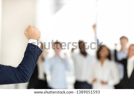 Successful confident businessman make speech show clenched fist demonstrate power and strength, excited diverse work team businesspeople support male leader together. Unity, leadership concept #1389051593