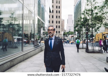 Successful confident groomed grey-bearded middle aged male businessman in expensive black suit and glasses walking confidently on New York street