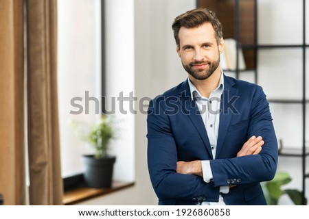 Successful confident young bearded brunet adult male entrepreneur businessman professional in business casual clothes standing with arms crossed folded at the modern home office and looking at camera Stock photo ©