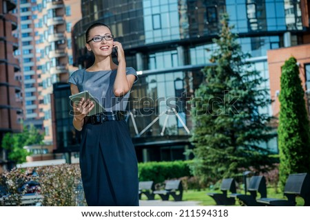 Successful conversation with the client. Business woman talking on a cell phone and looking forward. Successful business woman with glasses standing in the street in a business dress.