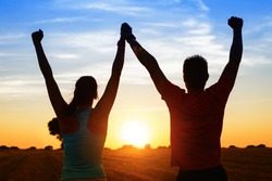 Successful couple of young athletes raising arms to golden summer sunset sky after training. Fitness man and woman with arms up celebrating sport goals after exercising in countryside field.