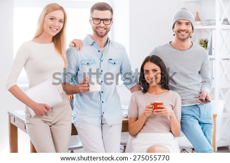 Successful creative team. Group of business people in smart casual wear looking at camera and smiling while leaning at the desk in office