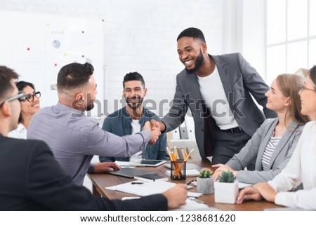 Successful deal. Two businessmen shaking hands, sitting at desk in office #1238681620