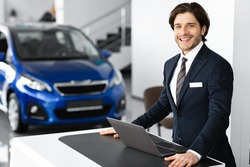 Successful Dealer. Car Sales Manager Standing At Desk In Luxury Dealership Office, Looking At Camera, Copyspace