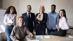 Successful diverse employees with team leader looking at camera, posing for corporate portrait in modern boardroom together, satisfied business people colleagues with boss standing in office