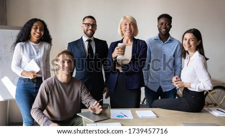 Successful diverse employees with team leader looking at camera, posing for corporate portrait in modern boardroom together, satisfied business people colleagues with boss standing in office Foto stock ©