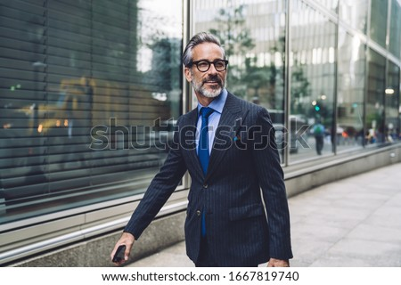 Successful elegant middle aged male executive in expensive suit walking purposefully on New York City street and turning head to side
