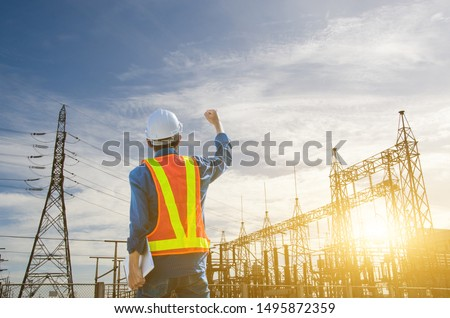 Successful engineer standing at the power substation against the sunrise background.