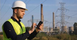 Successful EngineerWorker Man Working on Digital Tablet with Fossil Energy Power Plant Utility Building