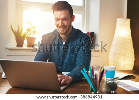 Successful entrepreneur smiling in satisfaction as he checks information on his laptop computer while working in a home office, sun flare behind