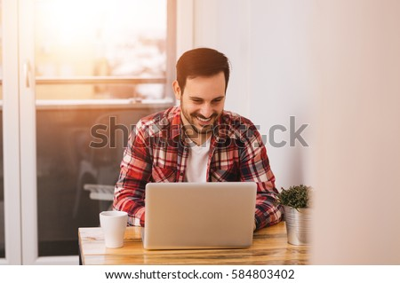 Successful entrepreneur smiling in satisfaction as he checks information on his laptop computer while working in a home office.