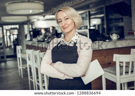 Successful entrepreneur. Successful entrepreneur wearing black apron standing in her own restaurant