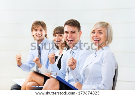 Successful excited Business people group team, young businesspeople smile hold fist ok yes gesture sitting in row line at office desk