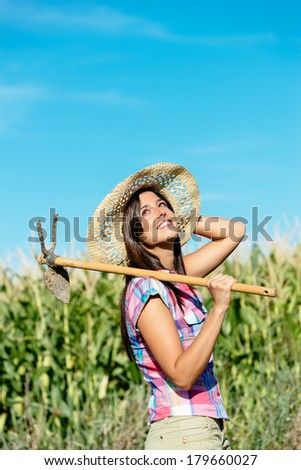 Successful female farmer carrying hoe in corn field. Countryside woman with work tool wearing straw hat and checkered shirt.