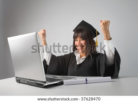 successful female graduate working with laptop