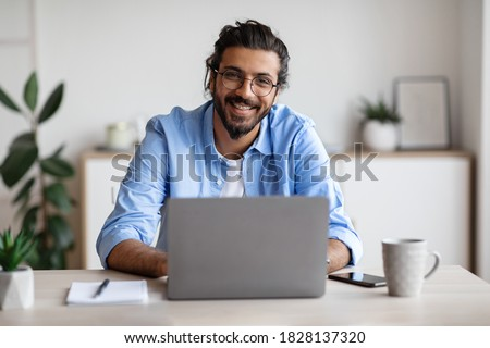 Successful Freelancer. Happy Millennial Indian Man Sitting At Desk With Laptop, Smiling And Posing At Camera While Working On Computer At Home Office, Wearing Eyeglasses And Braces, Free Space
