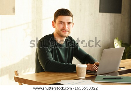 Successful Freelancer. Millennial Guy At Laptop Posing Smiling At Camera Sitting At Desk In Office.