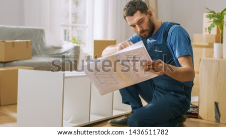 Successful Furniture Assembly Worker Reads Instructions to Assemble Shelf. Professional Handyman Doing Assembly Job Well, Helping People who Move into New House.