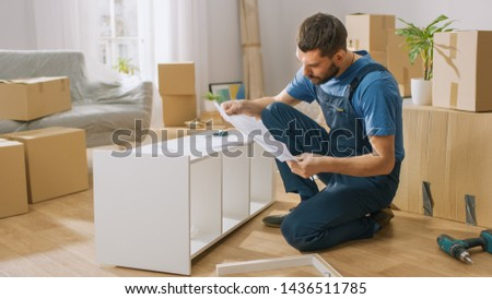 Successful Furniture Assembly Worker Uses Screwdriver to Assemble Shelf, Consults Instruction. Professional Handyman Doing Assembly Job Well, Helping People who Move into New House.