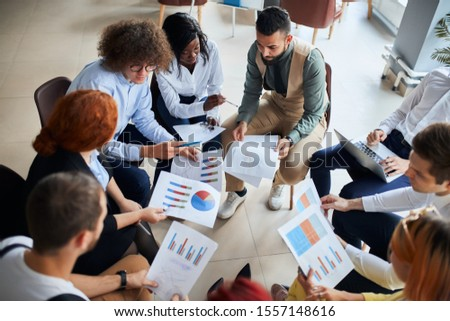 Successful gathering of business people, discussing new business ideas, using diagrams, sit together. Modern office background