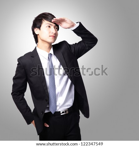 Successful handsome business man purposefully looking away to empty copy space isolated on gray background, mode is a asian male