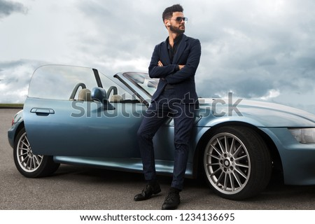 Successful, handsome man near the car.