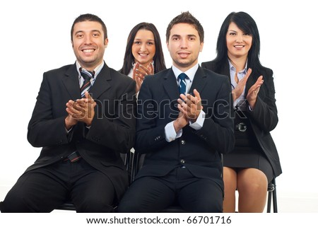 Successful happy business people sitting on chairs and clapping at conference