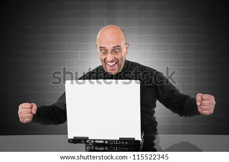 Successful happy man in front of his laptop with space for your text