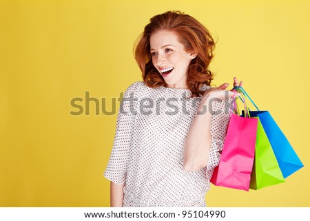 Successful happy shopper with three colourful shopping bags over her shoulder.
