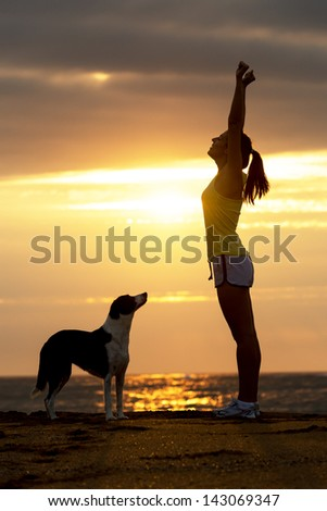 Successful happy woman with her dog raising arms celebrating victory on beautiful golden summer sunset in the beach.