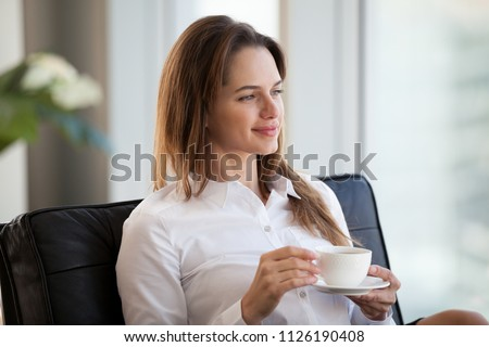 Successful happy young woman sitting in comfortable chair looking away drinking coffee at break, smiling thoughtful businesswoman contemplating relaxing with tea enjoying wellbeing in office hotel