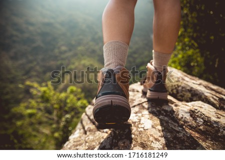 Photo of  Successful hiker enjoy the view on mountain top cliff edge