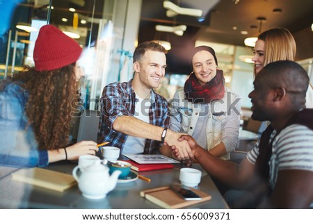 Successful informal meeting in cozy coffeehouse: cheerful designer shaking hand of his client while other participants looking at them with confident smiles