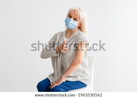 Successful Inoculation Against Coronavirus. Smiling Vaccinated Mature Woman In Surgical Mask Gesturing Thumbs Up Showing Shoulder With Patch After Covid-19 Vaccine Injection Sitting On Chair