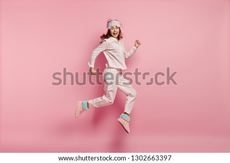Successful joyful female feels like winner, jumps high in air, wears casual pyjamas and eyemask, wakes up in high spirit, isolated over pink background. People, rest, emotions and sleeping concept #1302663397