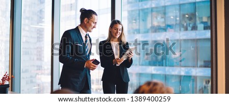 Successful male and female directors in formal wear reading news on web page during break from office cooperation, caucasian partners using company internet connection for communication via touch pad
