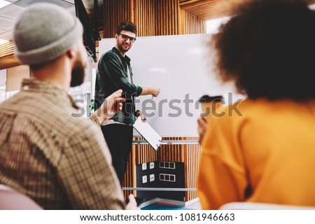 Successful male coach conducting seminar explaining information standing near white flipchart in university.Creative positive leader talking about business plan with students during workshop