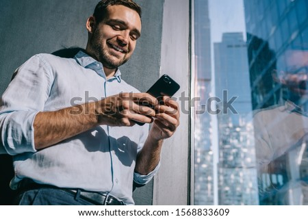 Successful male employer reading positive email message on smartphone device using 4g wireless connection for making business money exchange, happy Caucasian financial expert sending cellphone sms