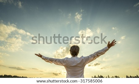 Successful man in elegant white shirt standing with his back to the camera with his arm spread widely towards beautiful majestic evening sky as he celebrates his success and prosperity.